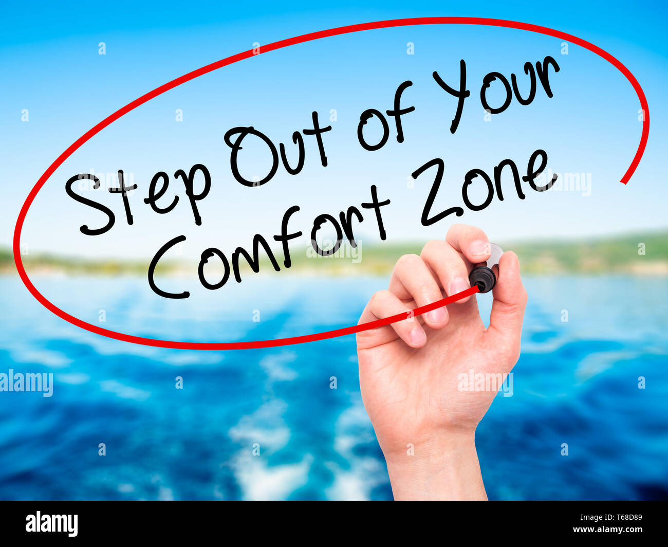 Man Hand writing  Step Out of Your Comfort Zone with black marker on visual screen. Stock Photo
