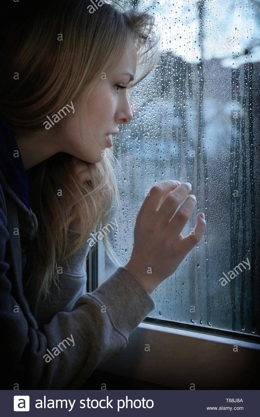 woman looking through window with raindrops - Stock Image