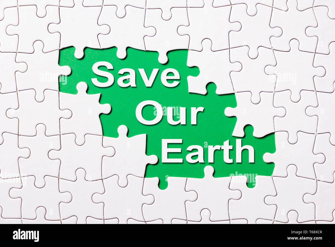 Save our earth word reveal under jigsaw puzzle Stock Photo