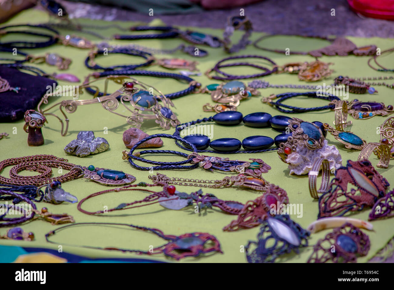 Handcrafted jewelery on a mat at the traditional local market of the colonial town of Villa de Leyva, in the Andean mountains of central Colombia. - Stock Image