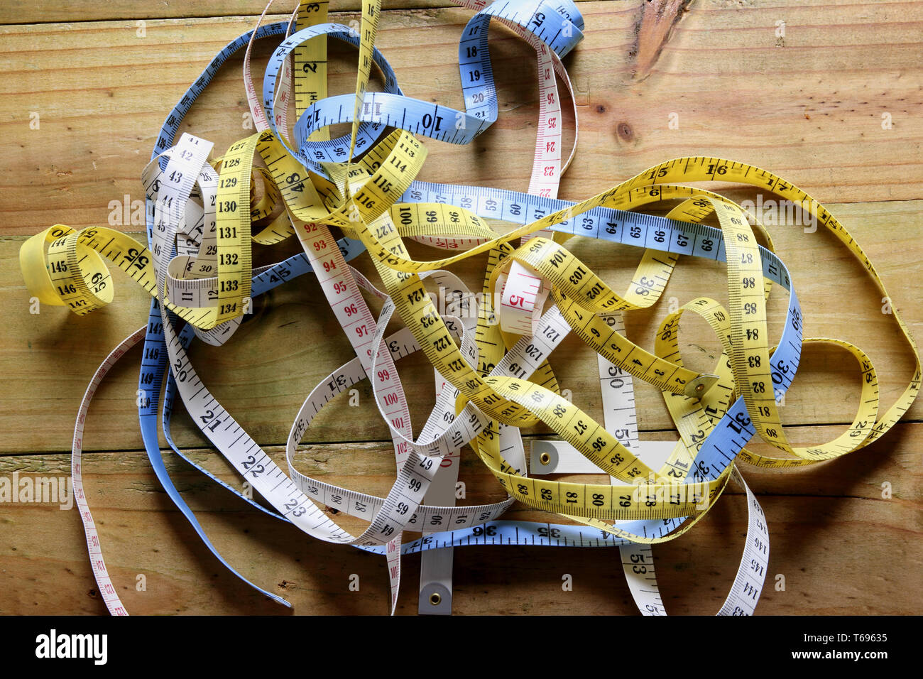 Tape Measures on Wooden Background - Stock Image