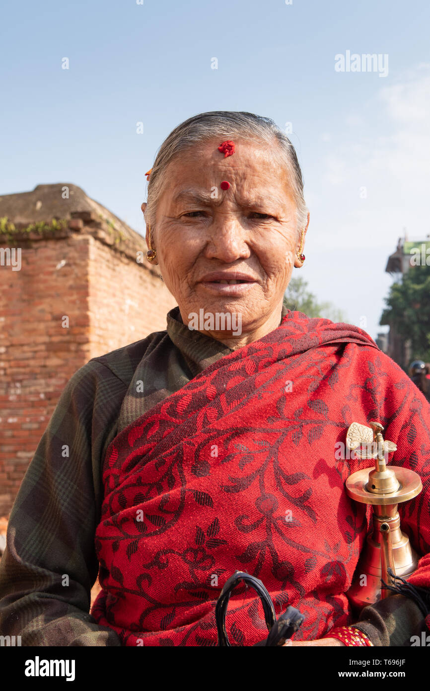Bhaktapur, Kathmandu Valley / Nepal - April 17th, 2019 - Nepali New Year celebrations showing elderly woman  at Durbar Square. Stock Photo