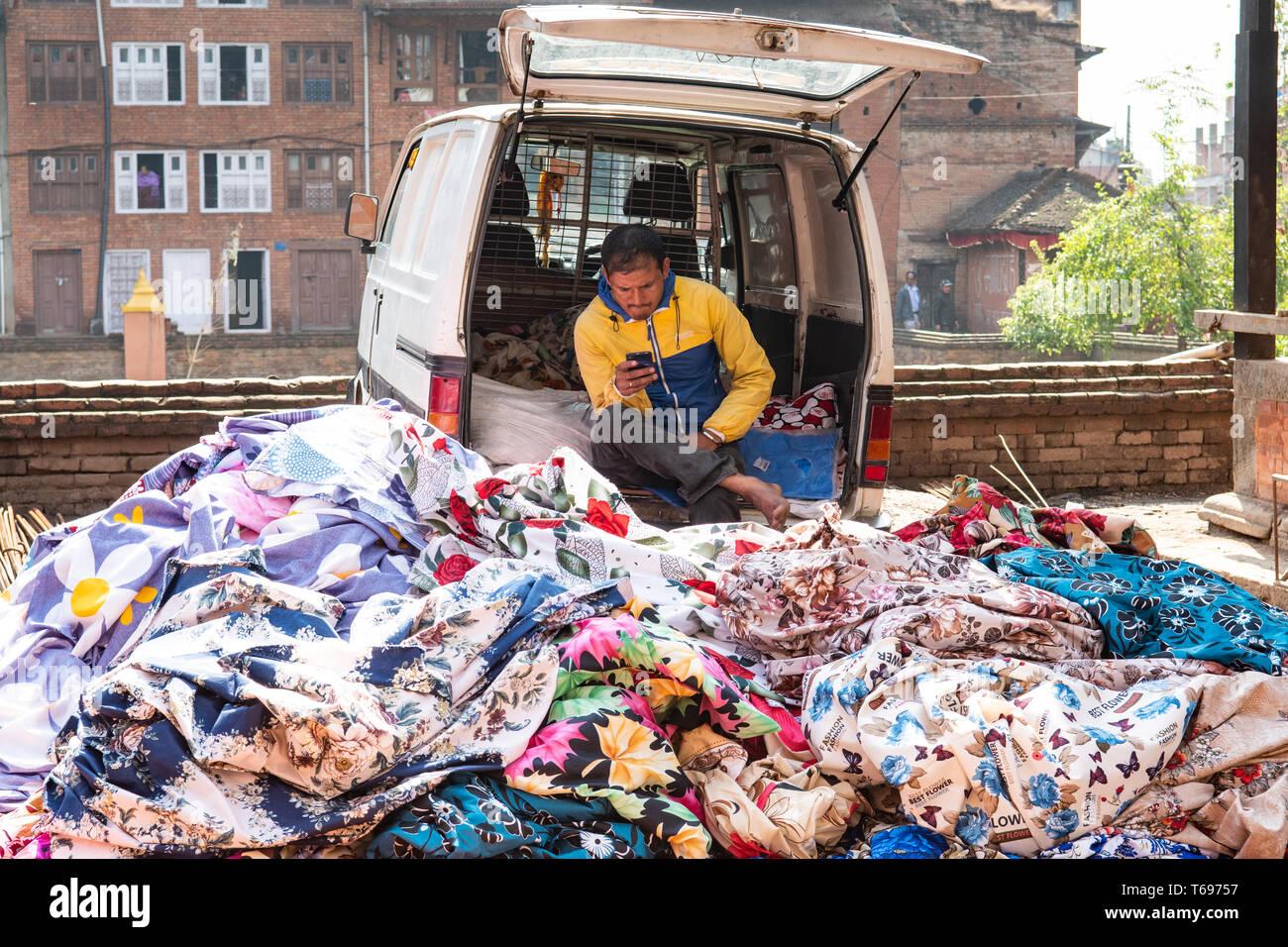 Bhaktapur, Kathmandu Valley / Nepal - April 17th, 2019 - Nepali man selling fabrics in the city. Stock Photo