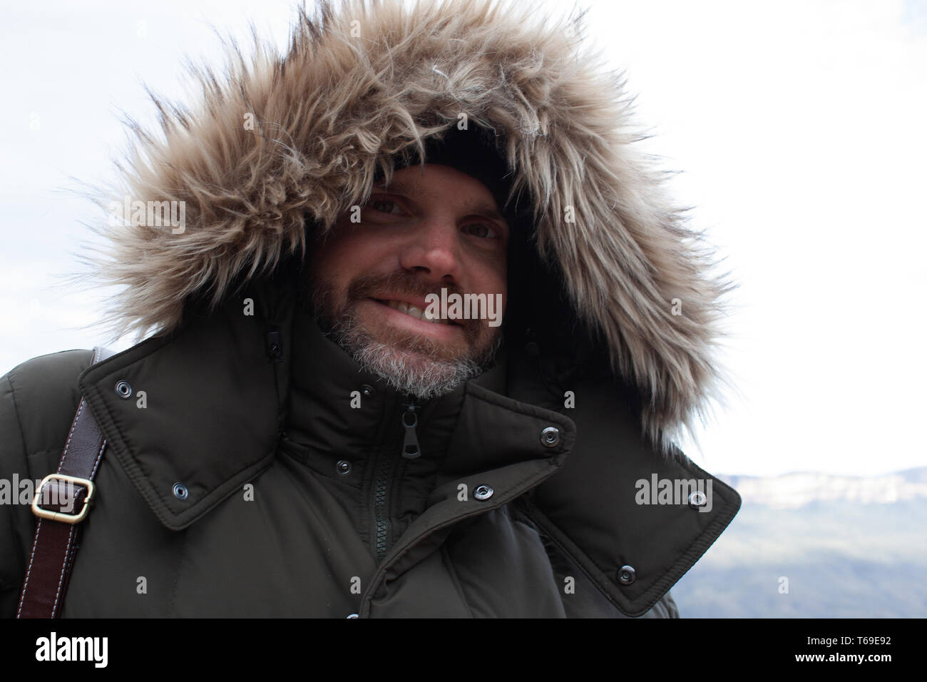 Bearded man in hooded jacket smiling - Stock Image
