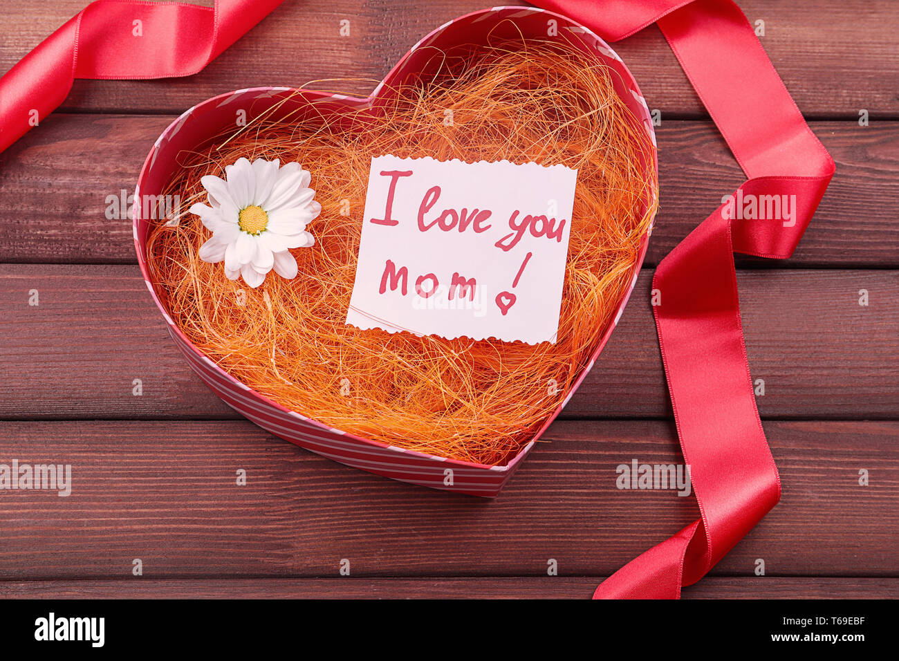 Gift box with greeting card for Mother's Day on wooden background Stock Photo