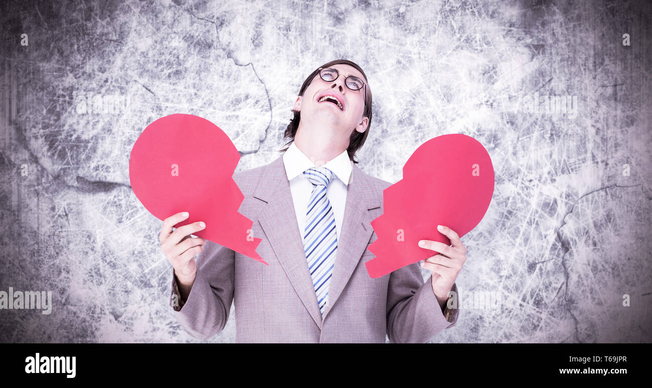 Composite image of geeky businessman crying and holding broken heart card - Stock Image