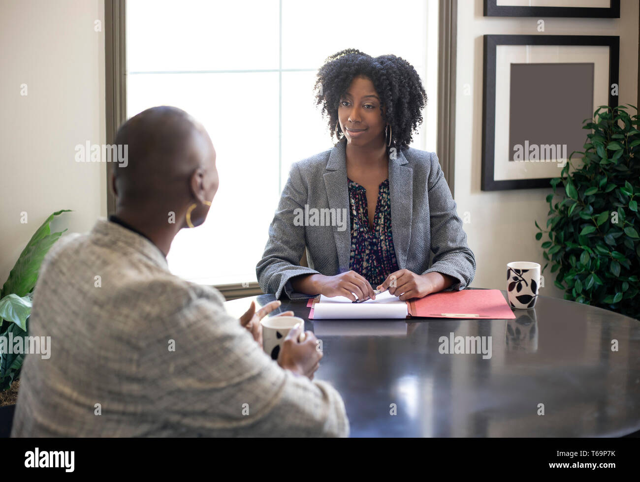 Black African American female businesswomen talking in an office.  The two women looks like a start up co workers or small business partners. - Stock Image