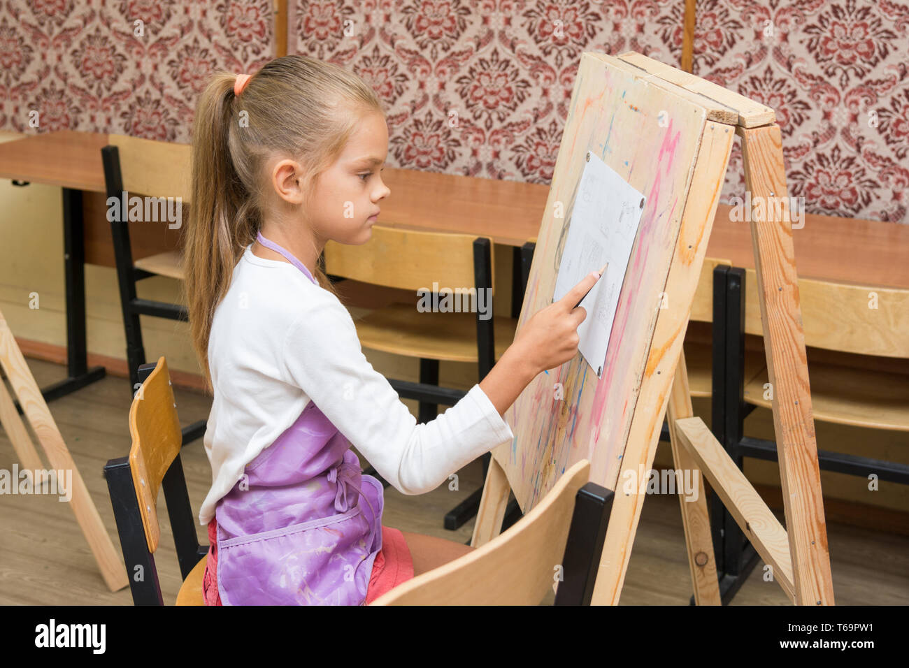 Girl artist paints on an easel to draw circle - Stock Image