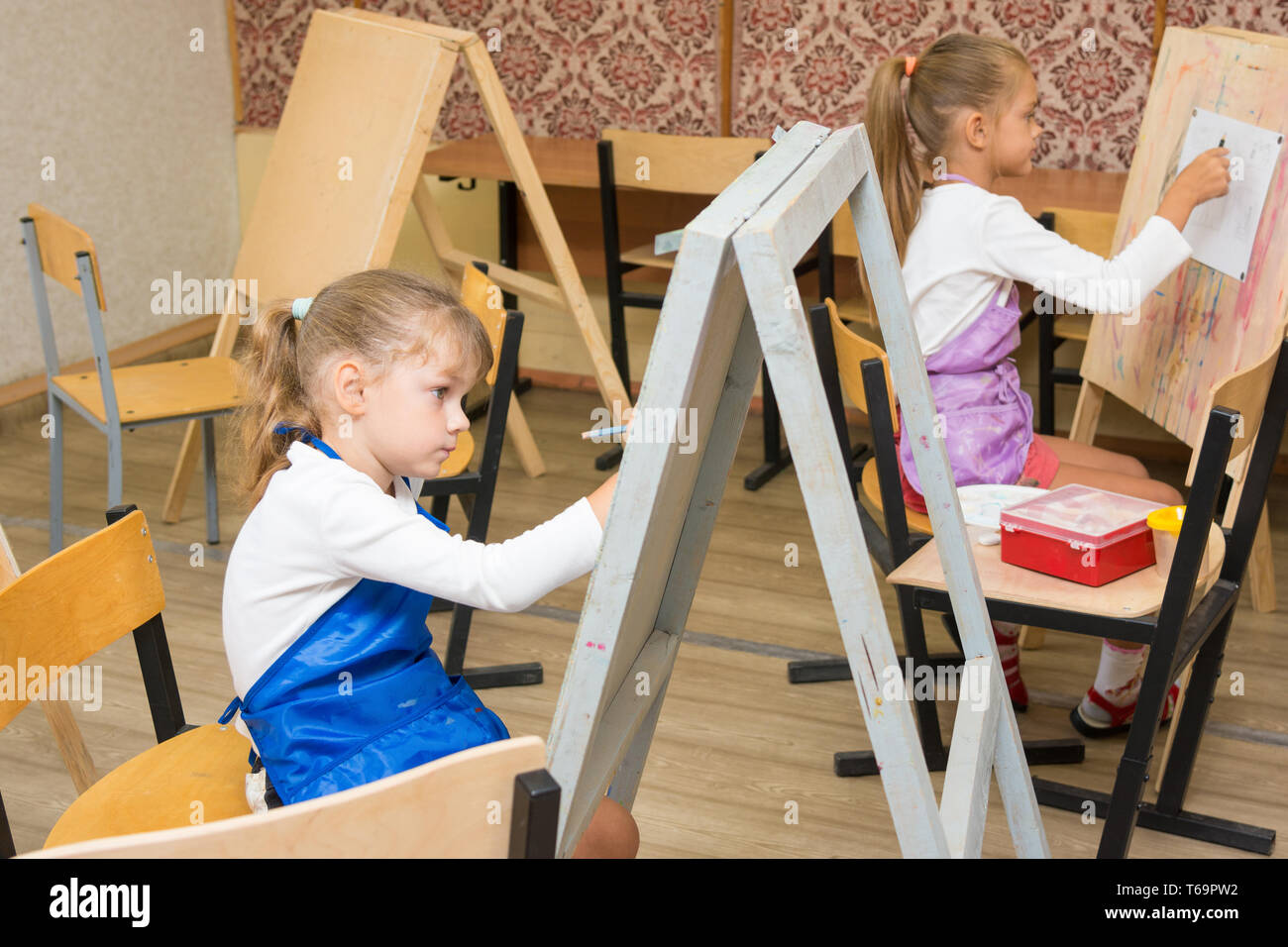 Two girls at a drawing lesson paint on easels - Stock Image