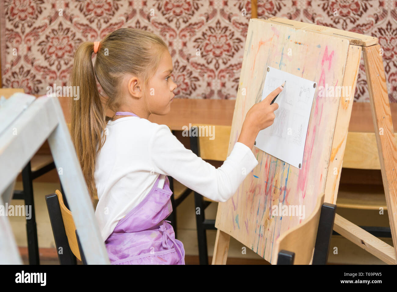 Girl paints on an easel in the drawing lesson - Stock Image