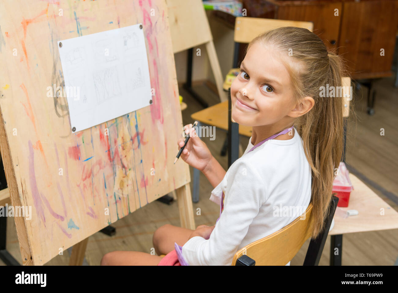 Girl happily looks into the frame on a drawing lesson - Stock Image