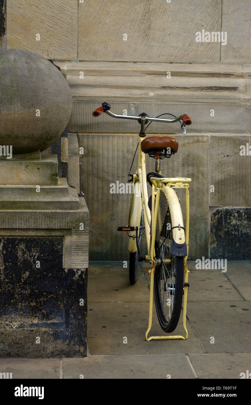 old yellow bicycle. leather seat with shock absorbers and wheel - Stock Image