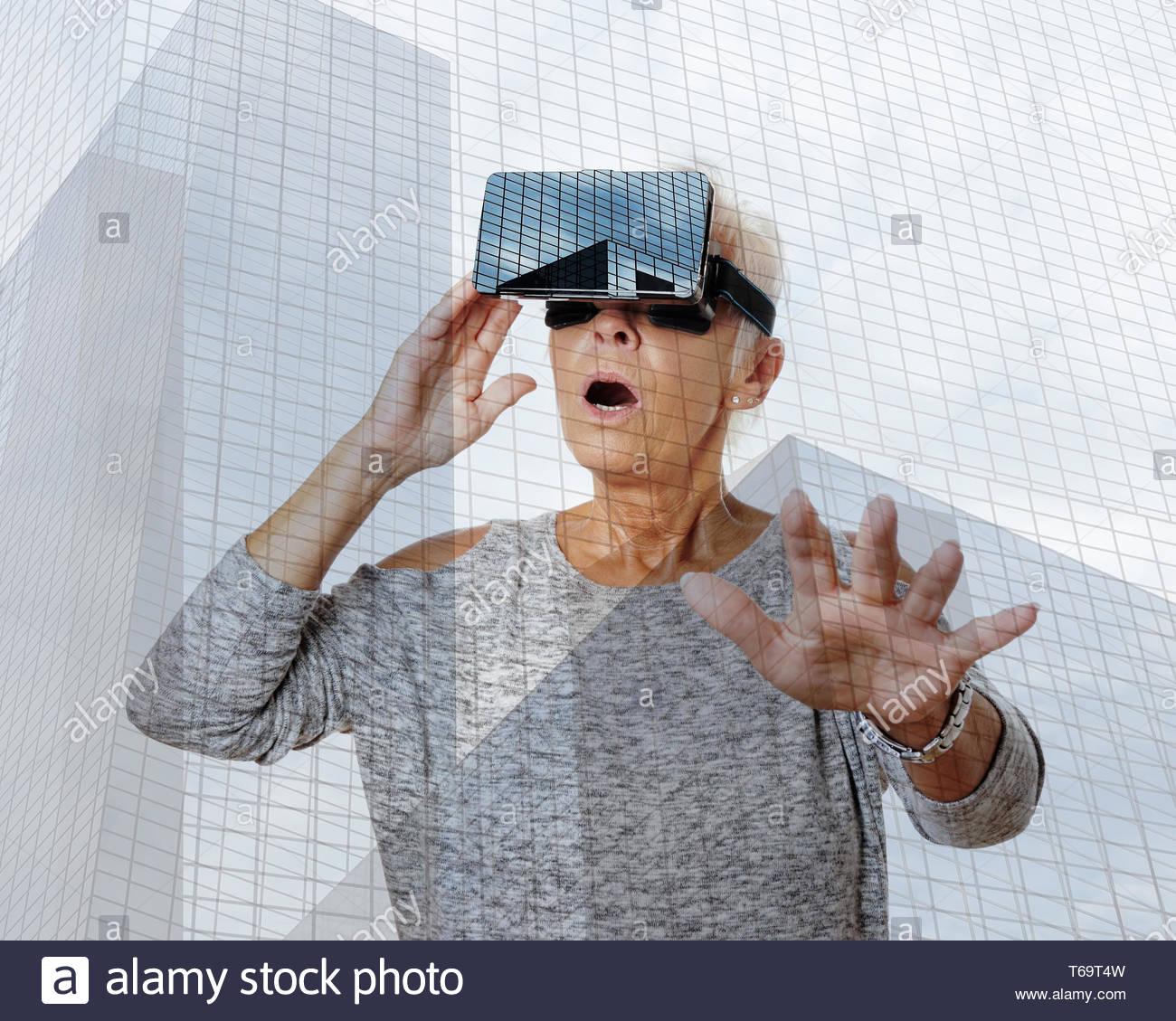 senior woman with VR virtual reality headset is stunned - Stock Image