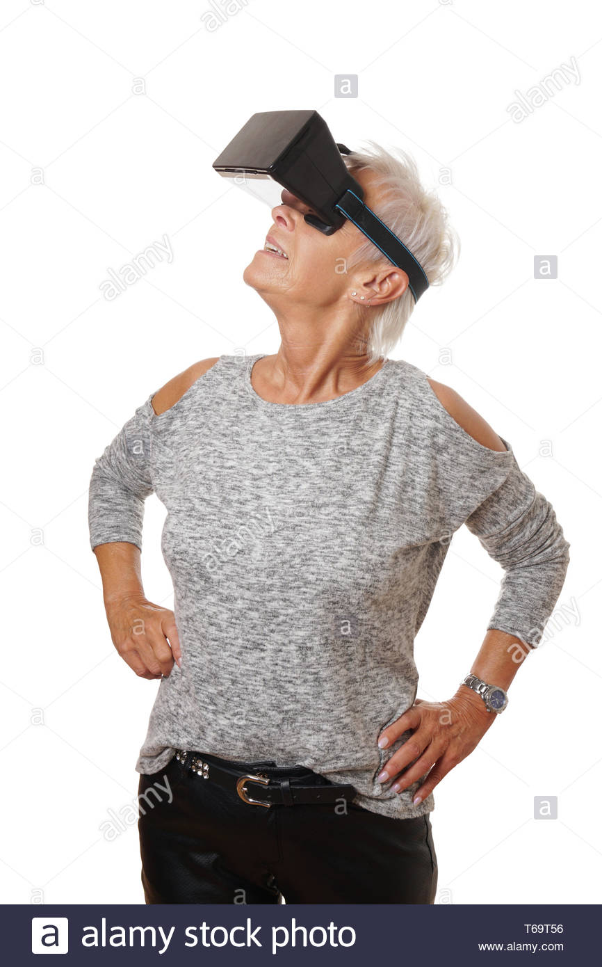mature woman wearing VR headset experiencing virtual reality - Stock Image