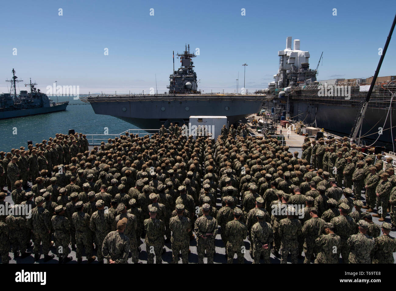 SAN DIEGO (April 26, 2019) The crew of the amphibious assault ship USS Bonhomme Richard (LHD 6), observes as Rear Adm. Cedric Pringle, Commander, Expeditionary Strike Group (ESG) 3, awards Religious Programs Specialist Seaman David Miller, from Salem, N.H., assigned to Bonhomme Richard, with the Navy and Marine Corps Commendation Medal during an awards ceremony on the roof of the ship's barge. Miller was awarded for his efforts in apprehending a woman threatening a church congregation on April 20, 2019. Bonhomme Richard is in its homeport of San Diego. (U.S. Navy photo by Mass Communication Sp Stock Photo