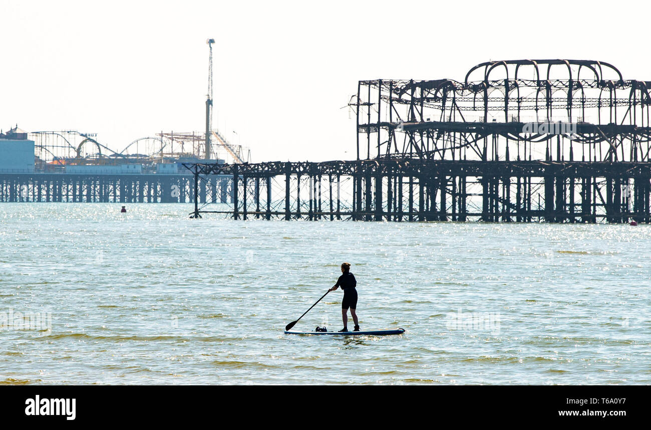 Brighton UK 30th April 2019 - A paddle boarder enjoys the warm sunny weather off Hove beach near the West Pier this morning with it forecast to reach into the high teens in some parts of the South East today. Credit: Simon Dack/Alamy Live News Stock Photo