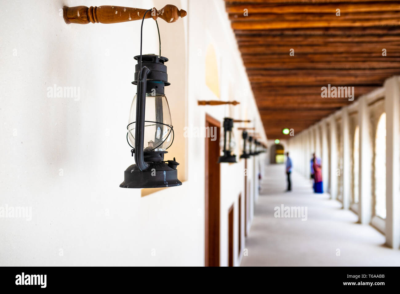 Landscape photo of a close-up view on a kerosene lamp in one of the open-air corridor forming a one point perspective in the Qasr Al-Hosn Fort in Abu  - Stock Image