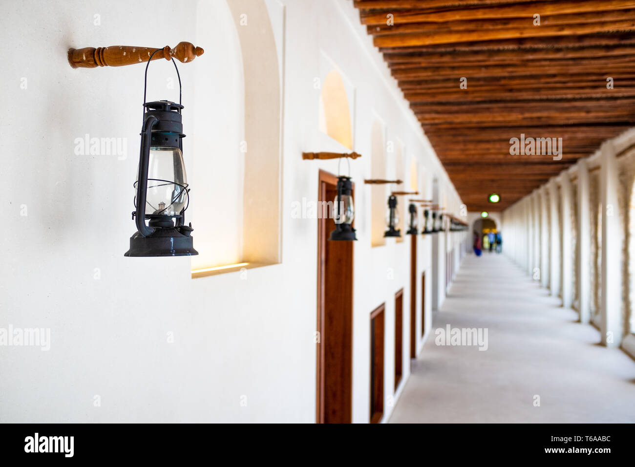 Landscape photo of a series of kerosene lamp in one of the open-air corridor forming a one point perspective in the Qasr Al-Hosn Fort in Abu Dhabi, Un Stock Photo