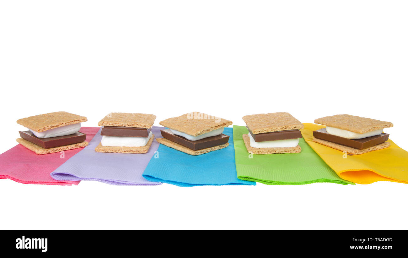 many s'mores lined up in a row on colorful napkins, ready for campfire party. Popular treat for Girl Scouts. - Stock Image
