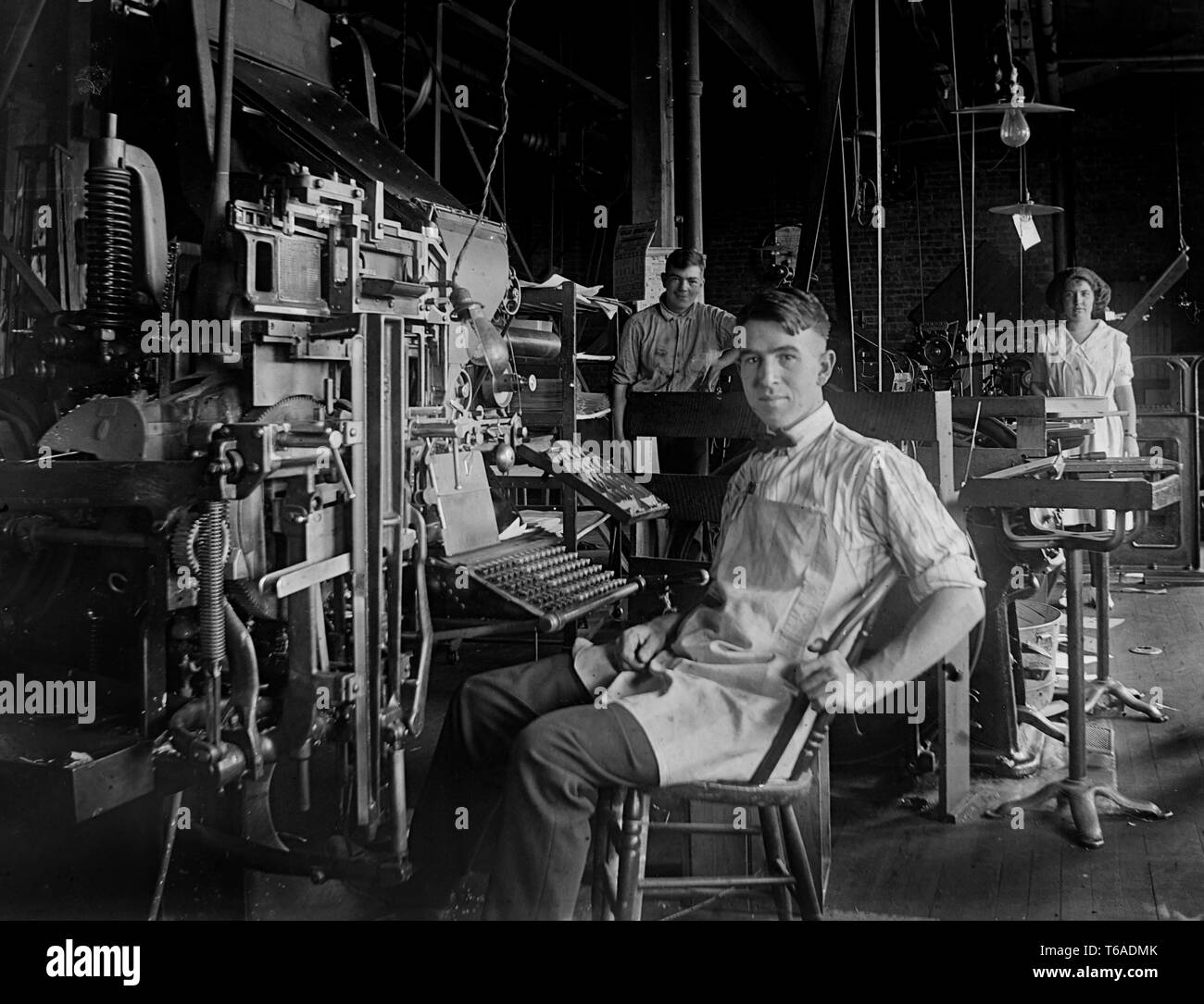 A young man sits at a typesetting machine in the back shop of a Pennsylvania newspaper, ca. 1910. - Stock Image