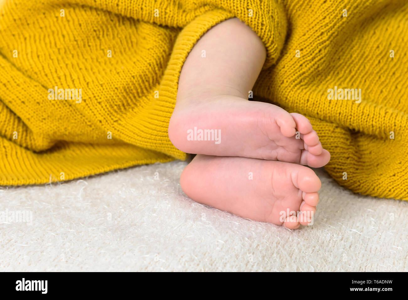 Close up of newborn baby feet on soft blanket - Stock Image