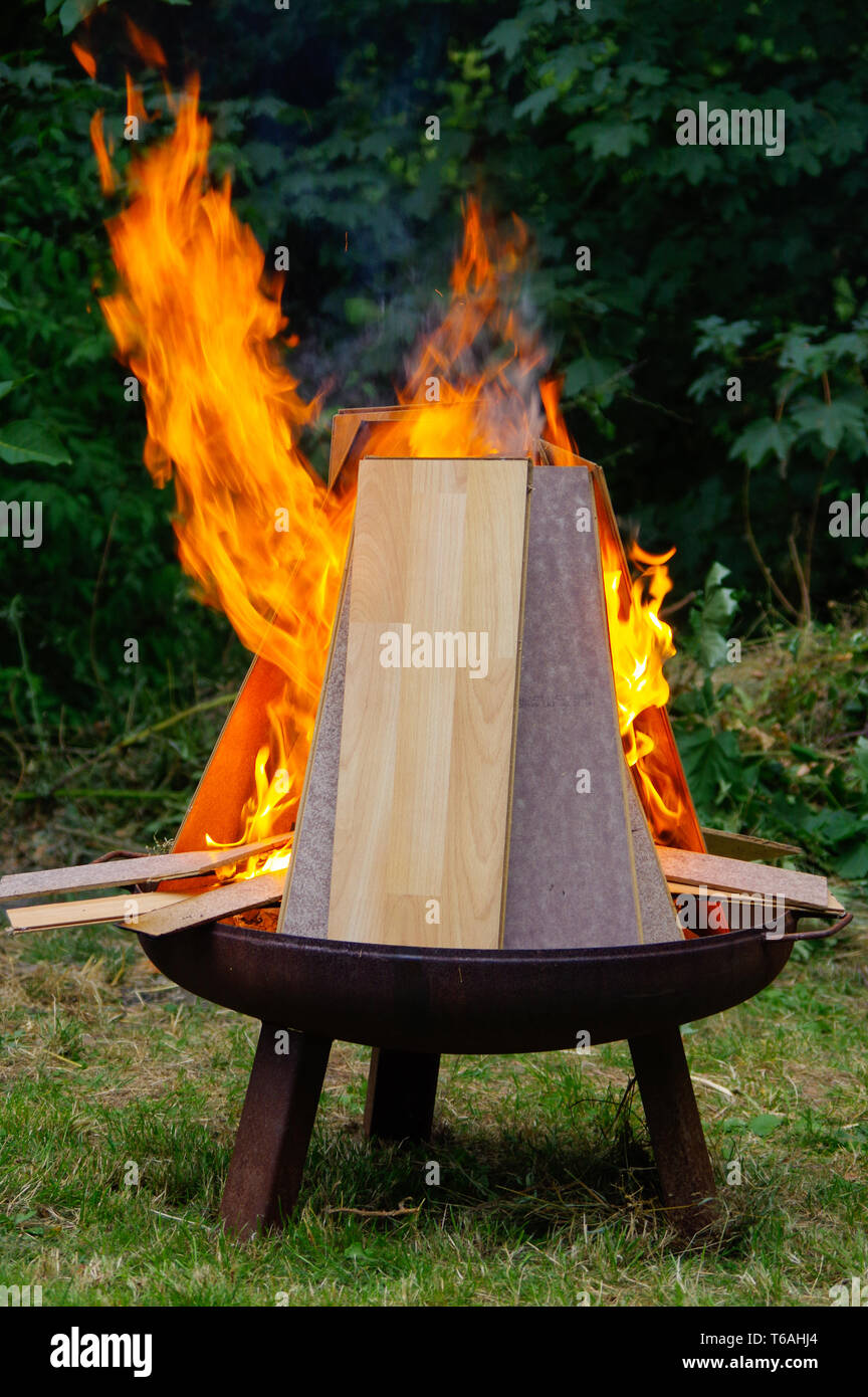 burning Laminate panels in open fire on a grill place - Stock Image