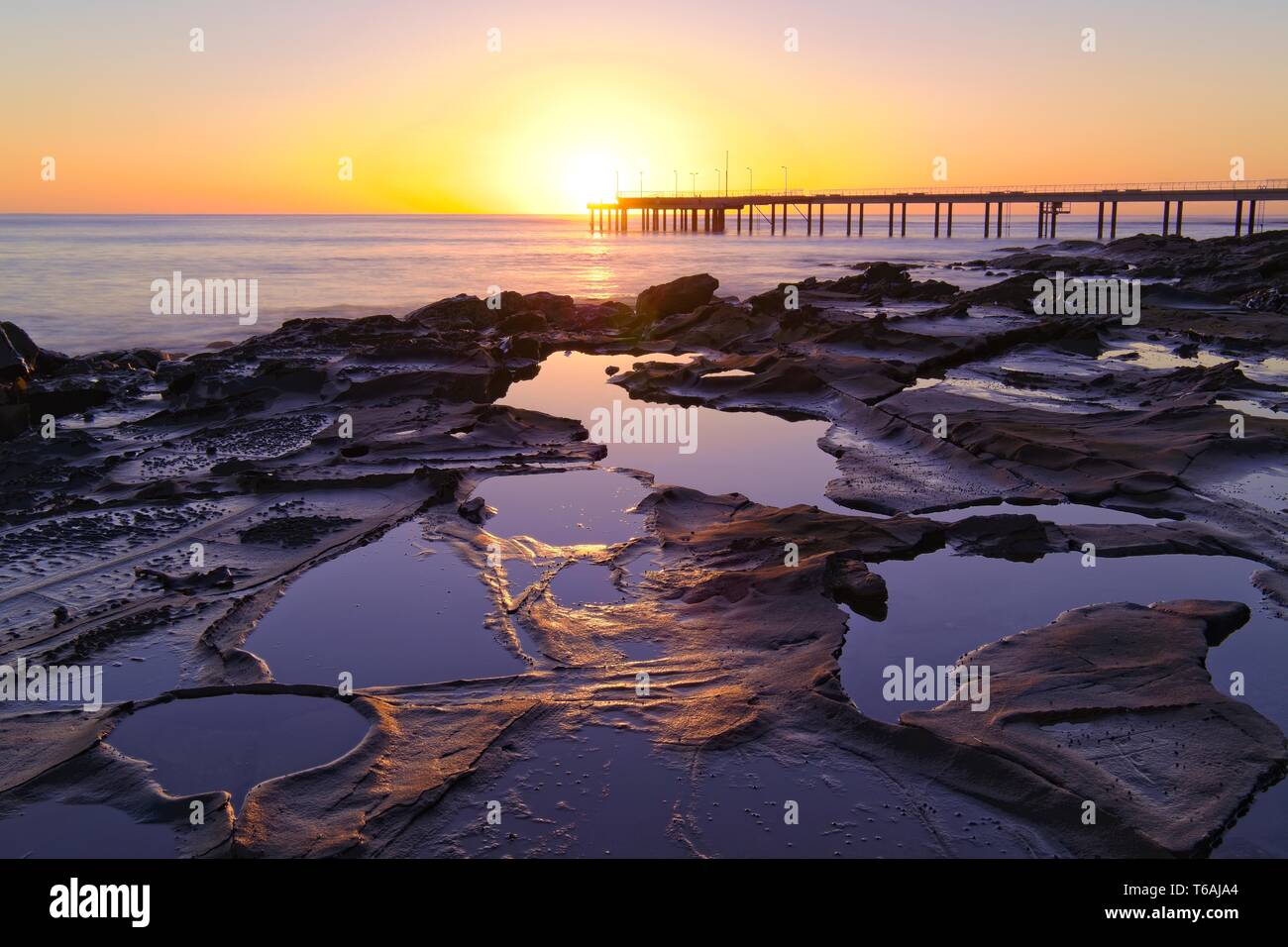 Looking over rocks and pools of water to Lorne Pier at sunrise - Stock Image