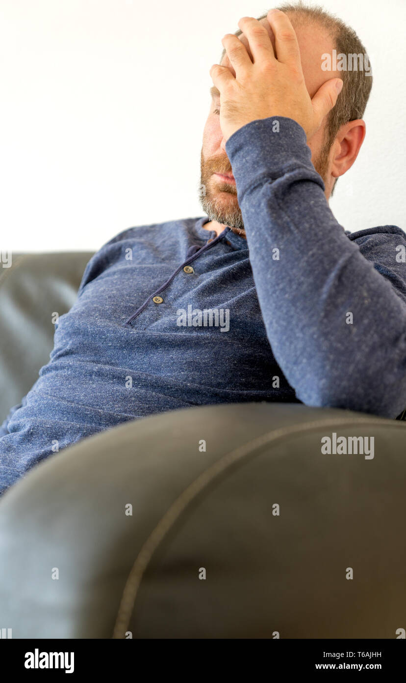 exhausted middle-aged man with a beard sits on sofa and rests his weary head in his hand - Stock Image
