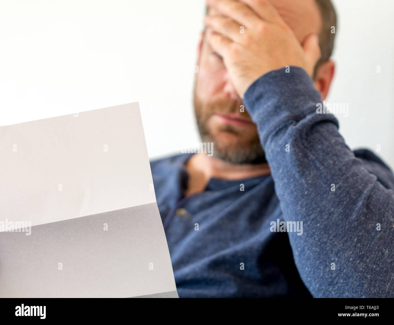 man in his forties sitting on a couch reachts emotionally to bad news he receives in a letter with selective focus and copy space - Stock Image