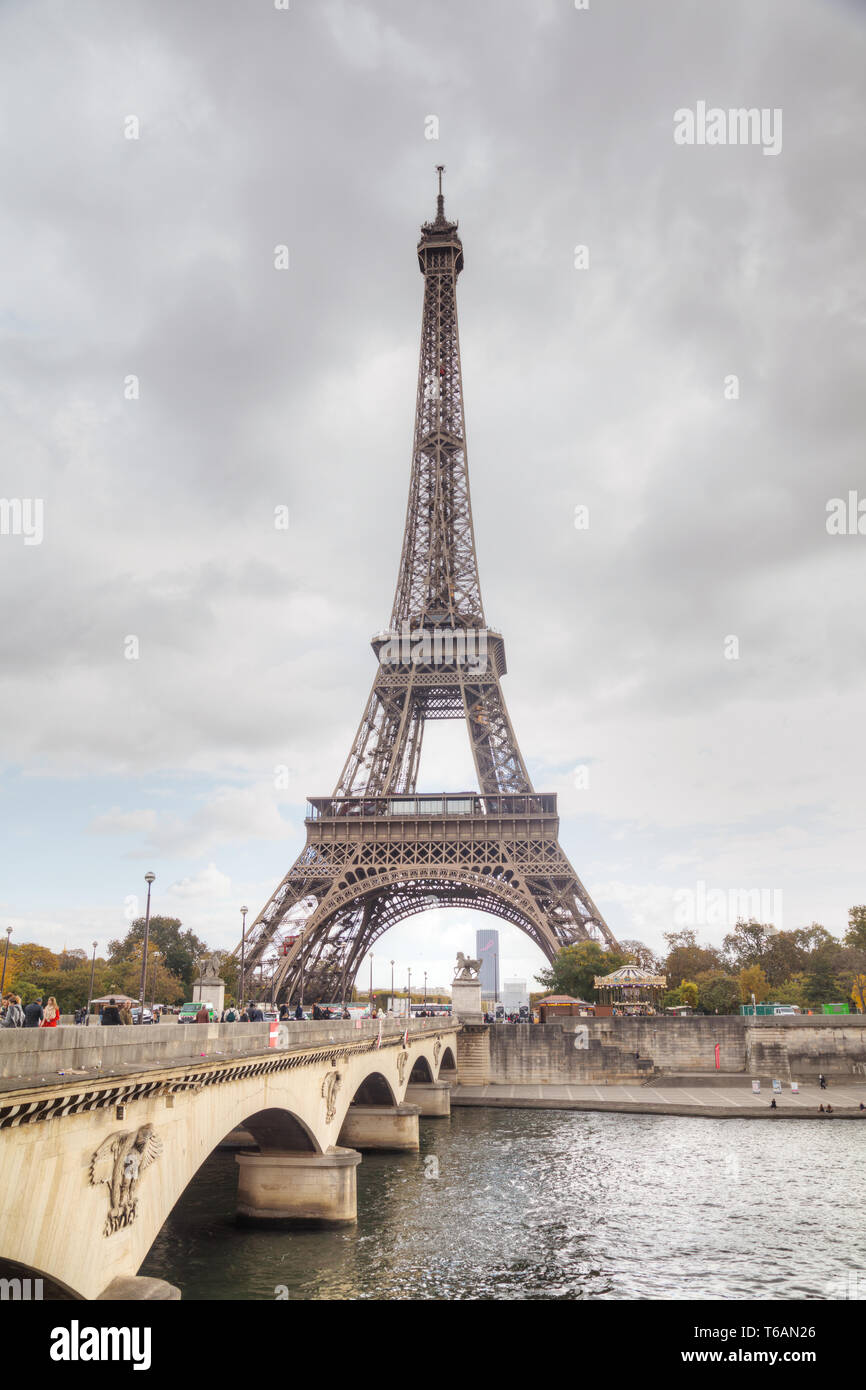Eiffel tower surrounded by tourists - Stock Image