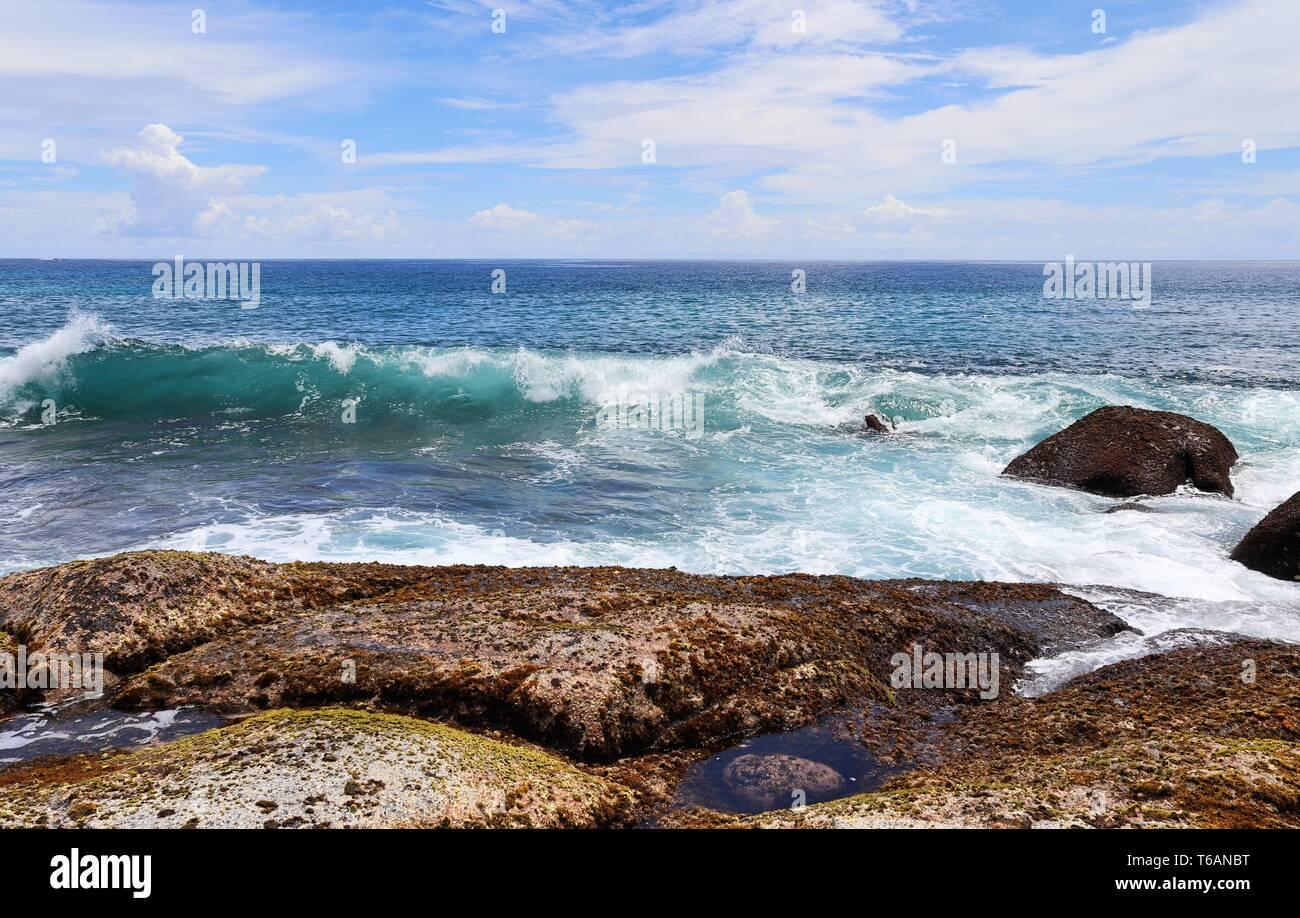 Beautiful splashing turquoise ocean waves at the white beaches on the paradise island Seychelles Stock Photo
