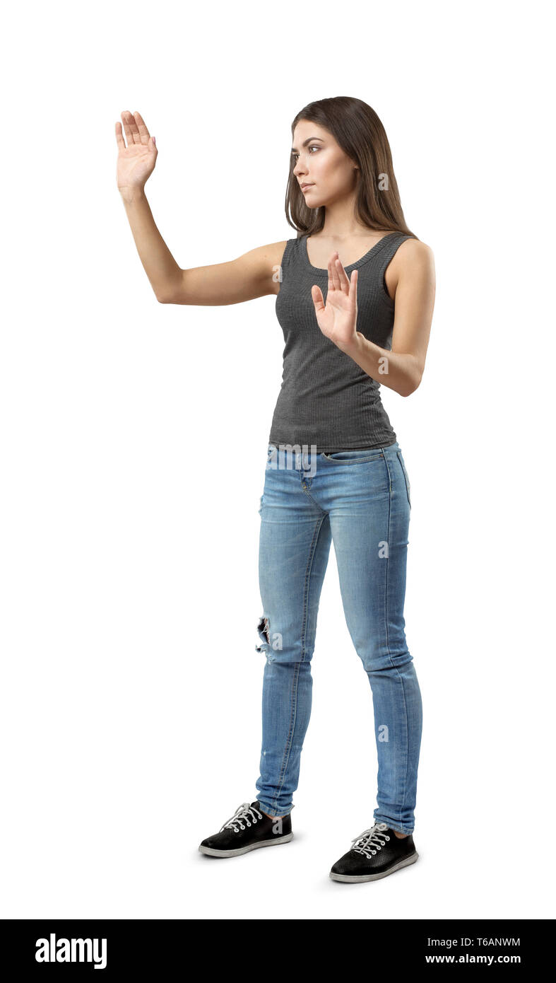 Fit beautiful woman in gray top and blue jeans standing in half-turn posing with hands raised as if touching invisible screen, isolated on white - Stock Image