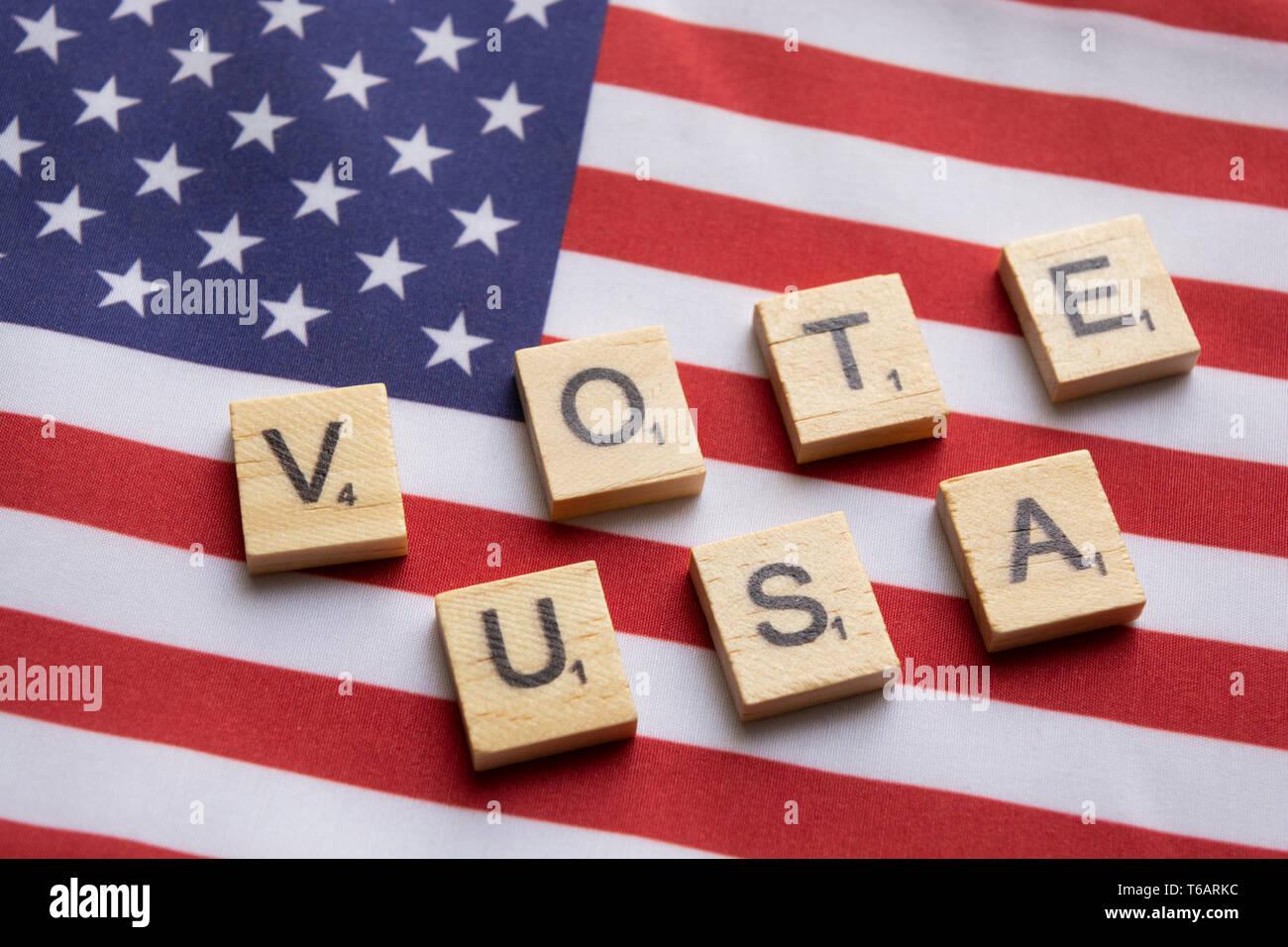 Maski, India 26, April 2019 : Vote USA wooden block letters on US flag - Stock Image
