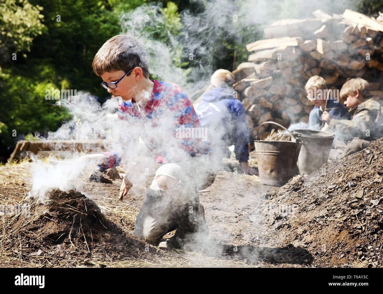 boys with smoking charcoal pile, Ennepetal, Ruhr Area, North Rhine-Westphalia, Germany - Stock Image