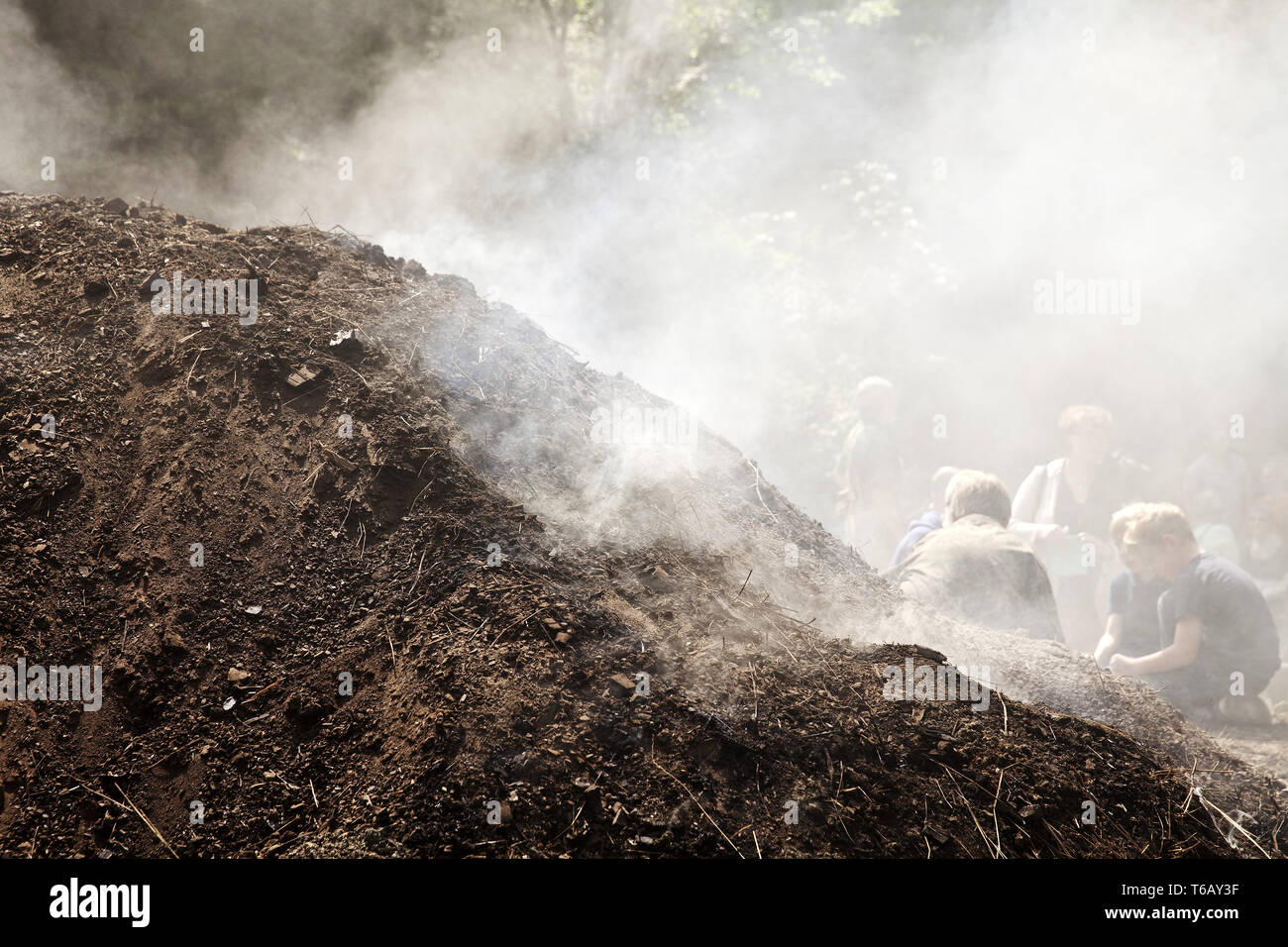 smoking charcoal pile, Ennepetal, Ruhr Area, North Rhine-Westphalia, Germany - Stock Image