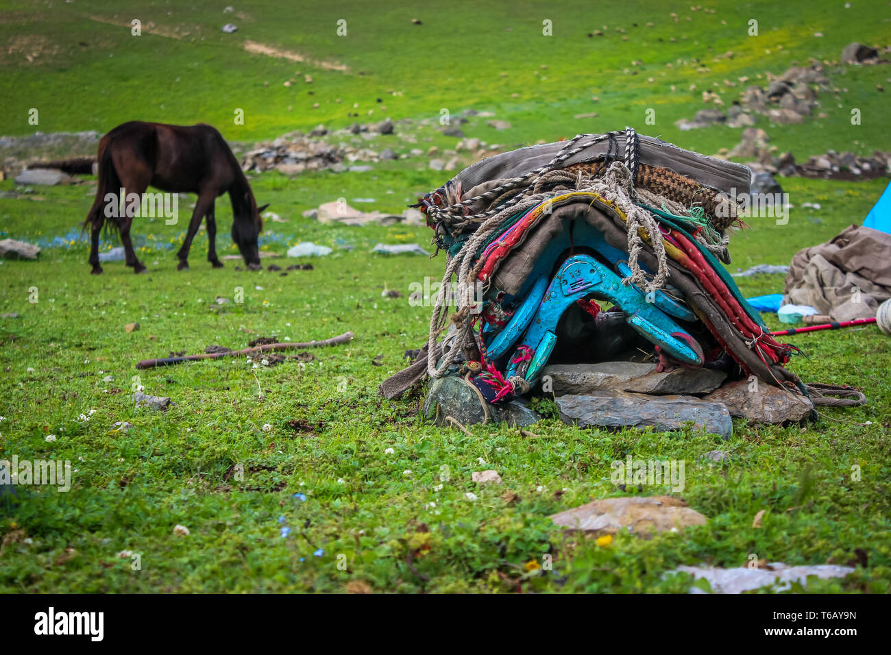 Saddle of a horse loaded with rags of Bakerwals in Kashmir. A horse in the background. - Stock Image
