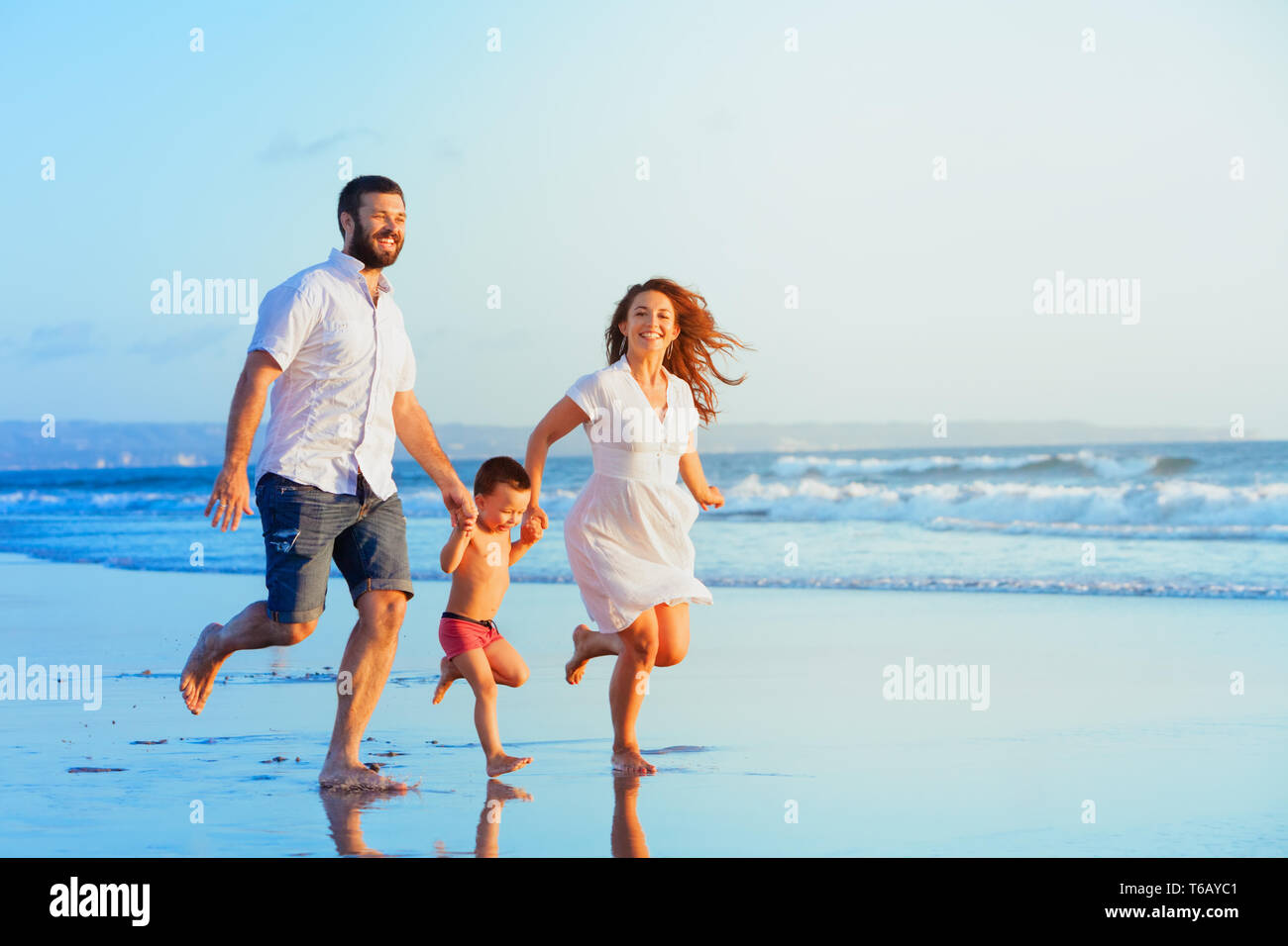 Happy family - young father, mother, baby son run together, child jump with fun by water pool along sunset sea surf on tropical beach. Travel lifestyl - Stock Image