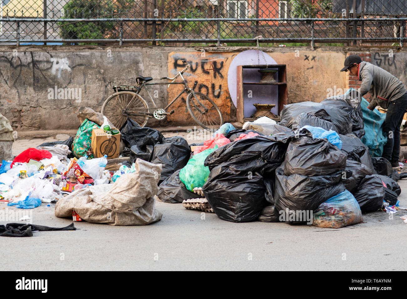 Kathmandu, Nepal - April 20th, 2019 - Garbage collector sorting through piles of trash early in the morning in the street. - Stock Image
