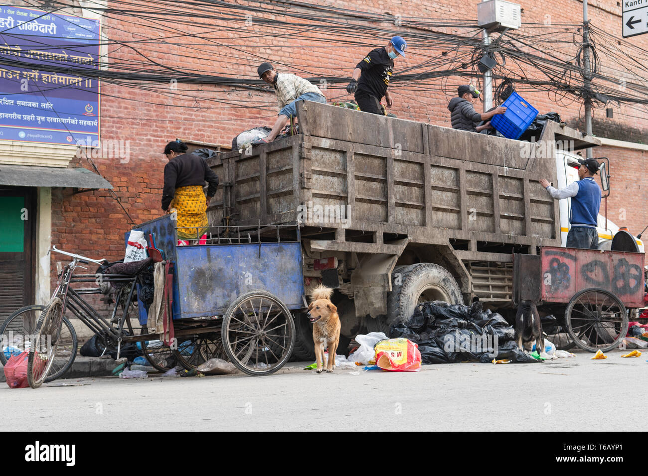 Kathmandu, Nepal - April 20th, 2019 - Garbage collectors and dogs sorting through piles of trash early in the morning in the street. - Stock Image