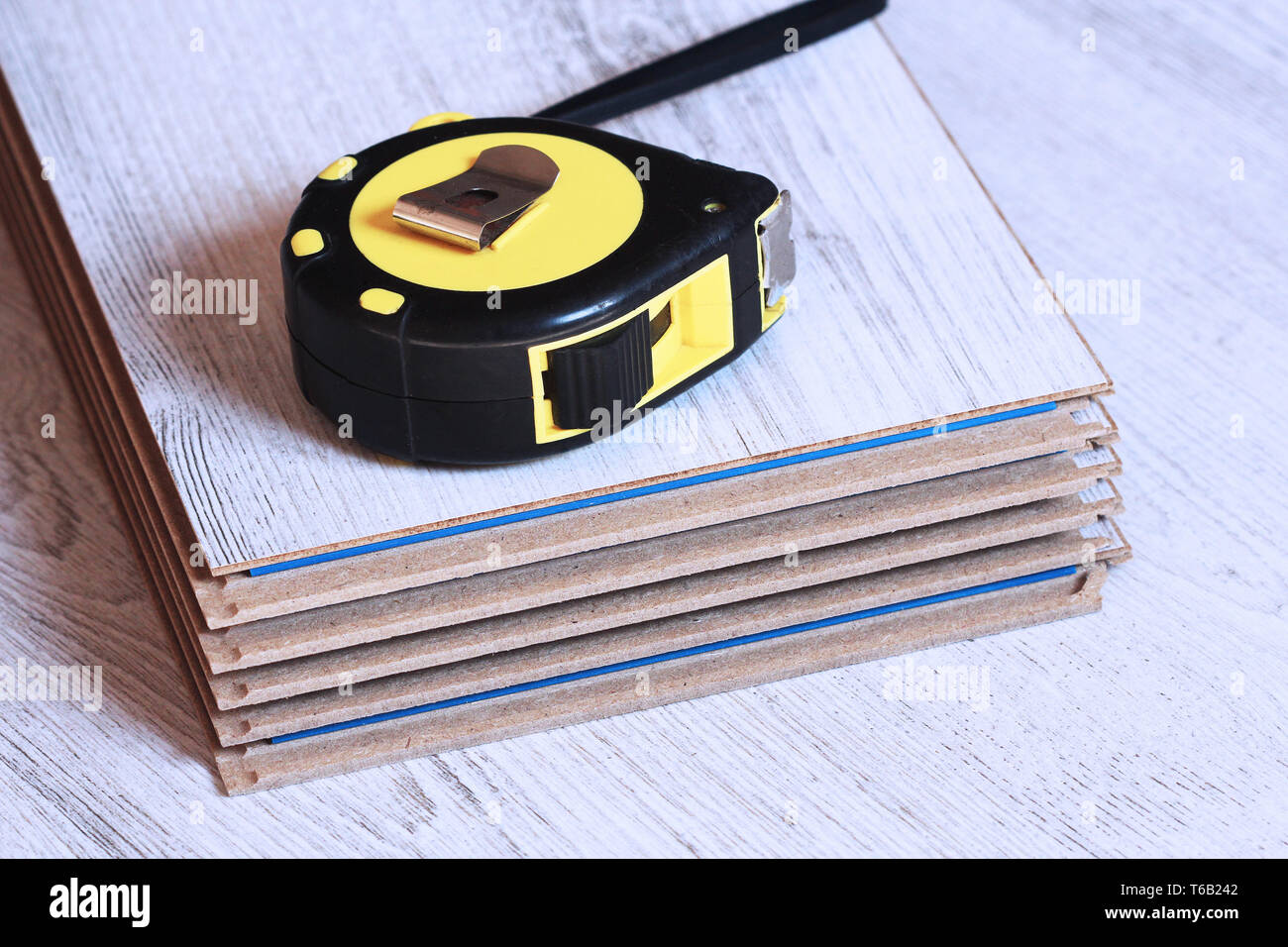 Laminate floor planks and tools on wooden background - Stock Image