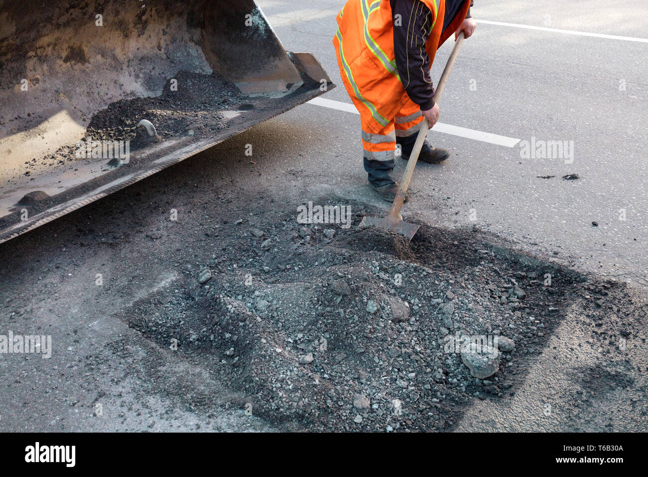 the road maintenance worker throws the old asphalt into the excavator's bogie in road construction - Stock Image