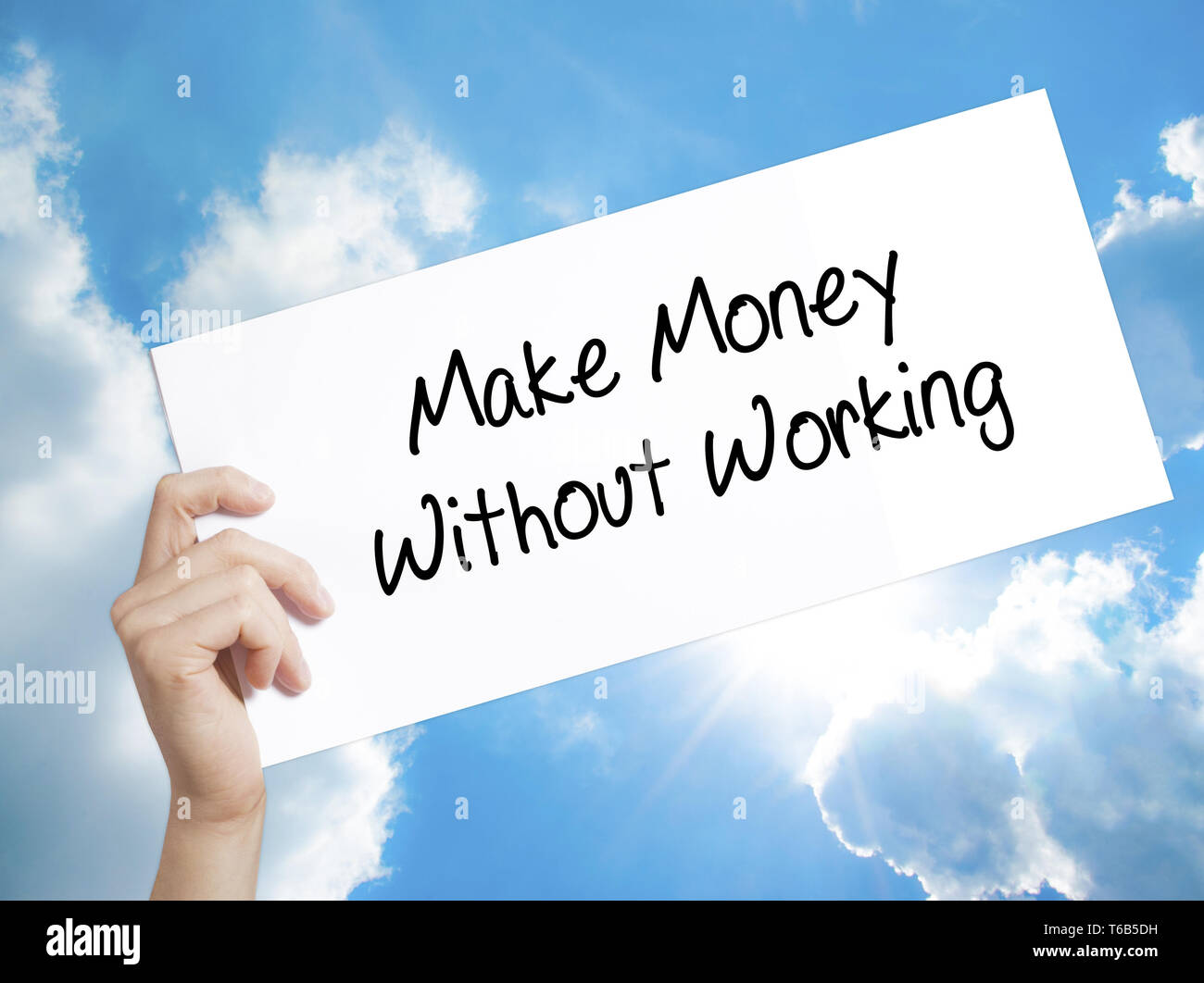 Make Money Without Working Sign on white paper. Man Hand Holding Paper with text. Isolated on sky background Stock Photo