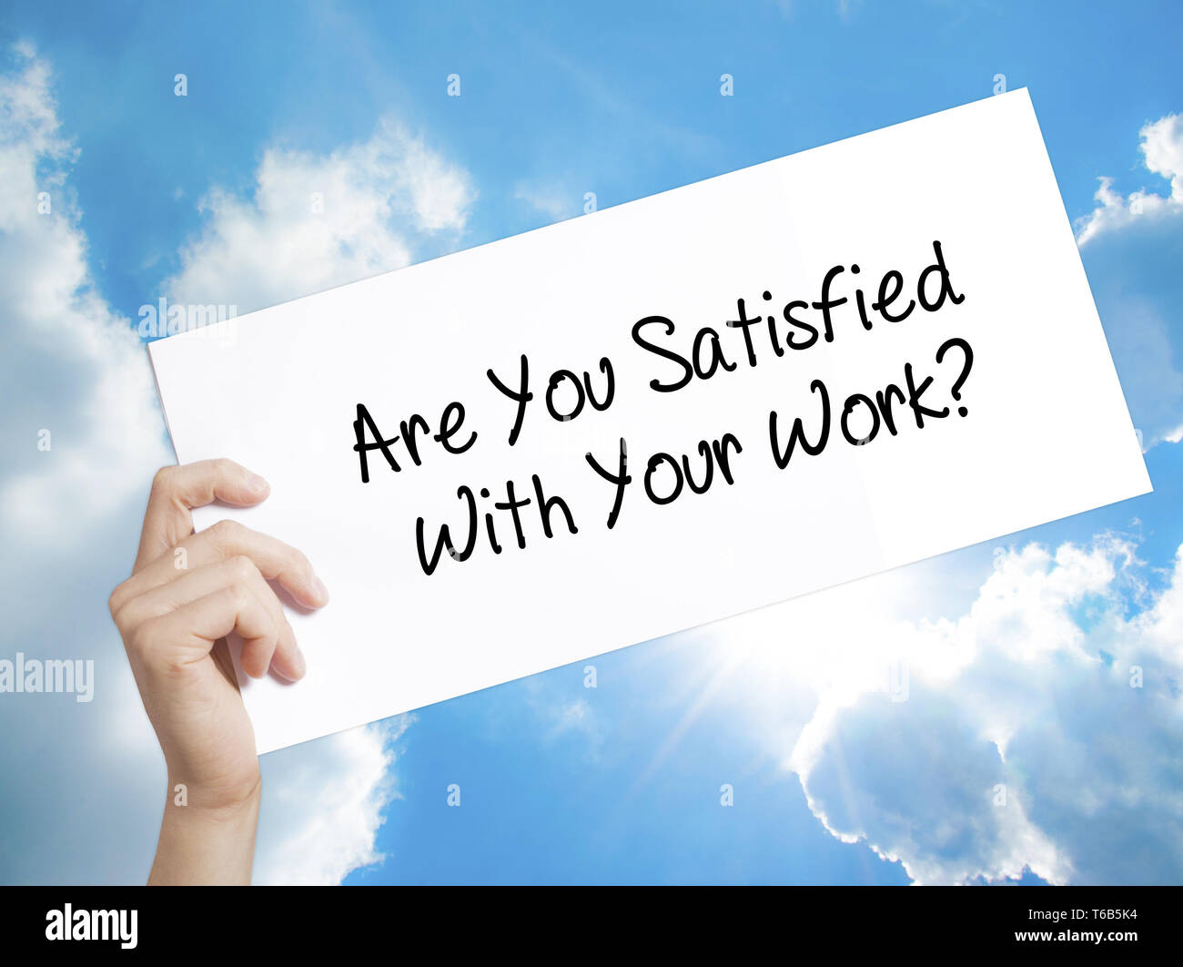Are You Satisfied With Your Work? Sign on white paper. Man Hand Holding Paper with text. Isolated on sky background - Stock Image