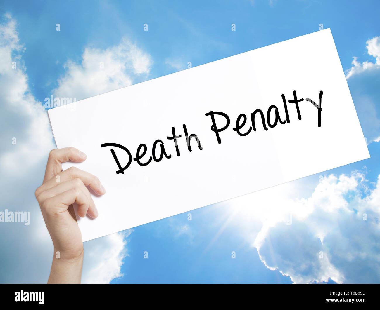 Death Penalty Sign on white paper. Man Hand Holding Paper with text. Isolated on sky background. - Stock Image