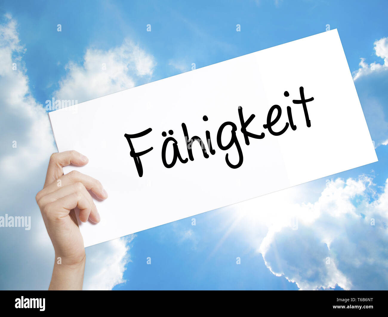 Fahigkeit (Ability in German) Sign on white paper. Man Hand Holding Paper with text. Isolated on sky background Stock Photo