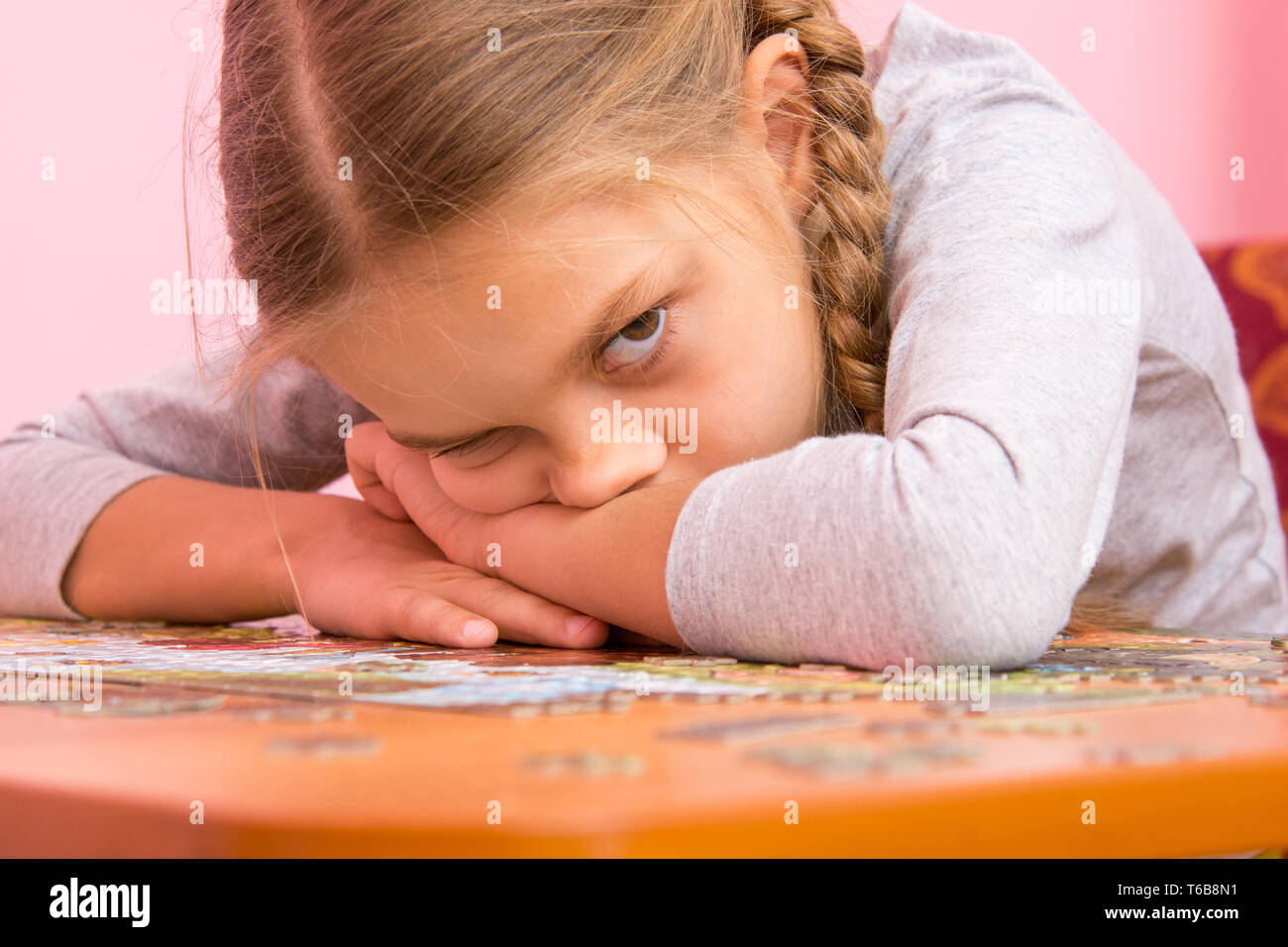 The girl was very tired assemble a picture from puzzles - Stock Image