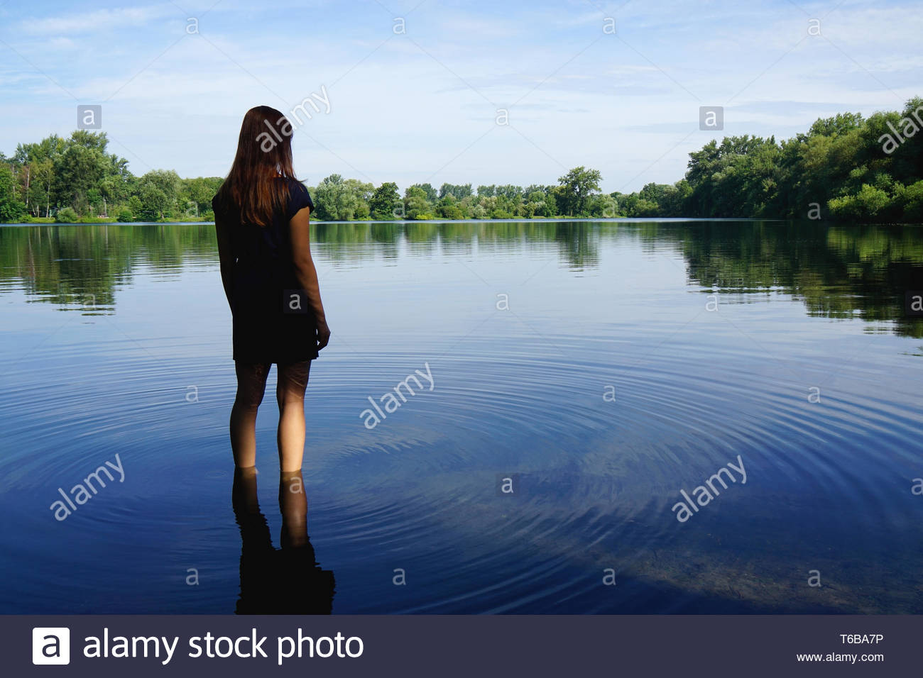 young woman standing in lake Stock Photo