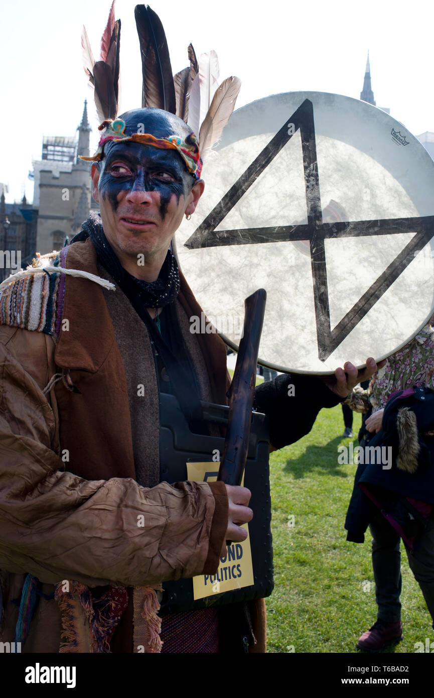 Extinction Rebellion protest, London . Parliament Square. A man with black oil-like paint on his face beats a drum with the XR symbol on it. - Stock Image