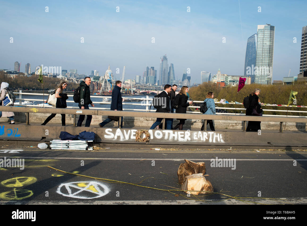 Extinction Rebellion protest, London . Waterloo Bridge. Commuters walk over the bridge closed to traffic by the XR protest. - Stock Image