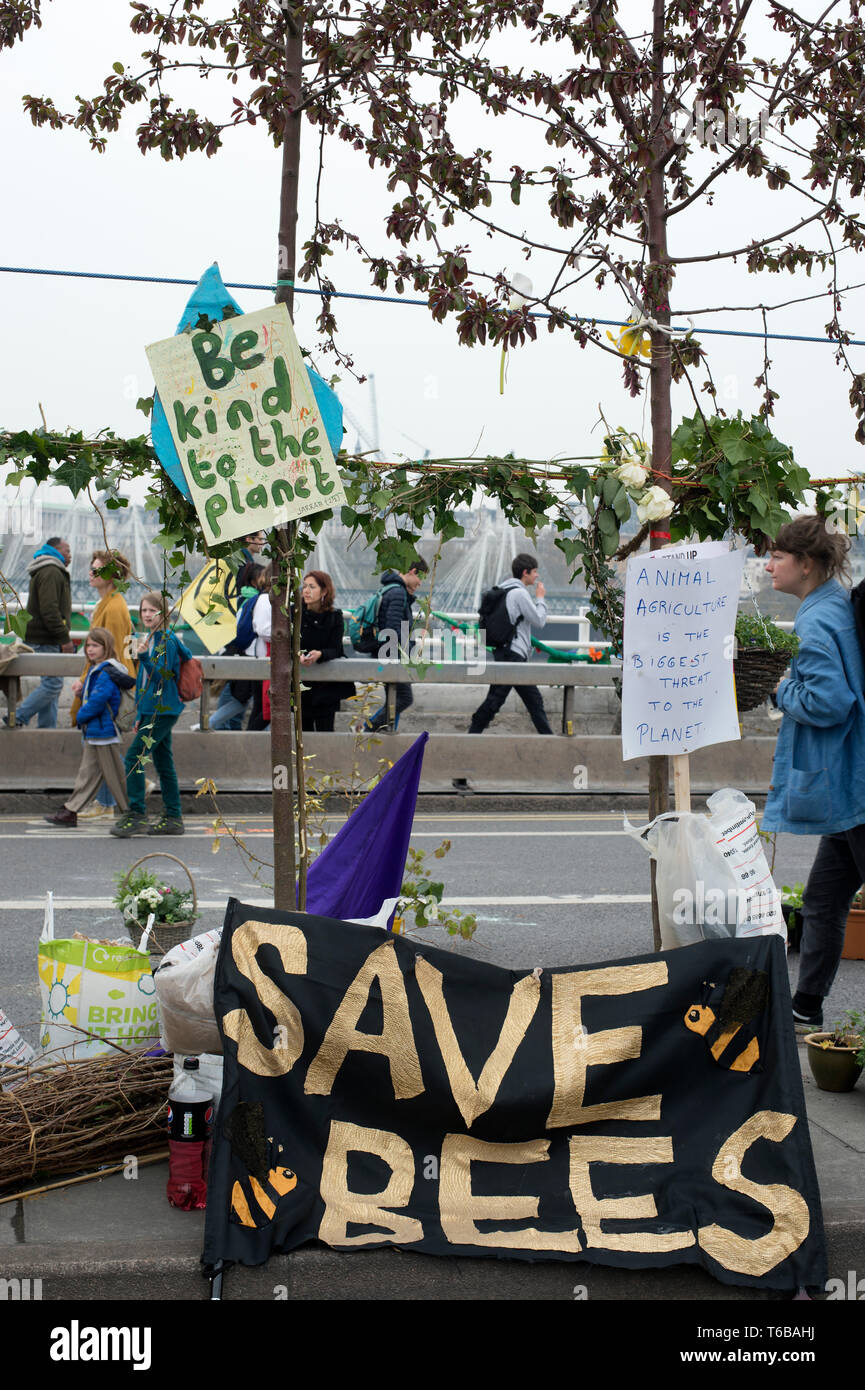 Extinction Rebellion protest, London . Waterloo Bridge. People walk over the bridge closed to traffic by the XR protest which now has a garden and a b - Stock Image